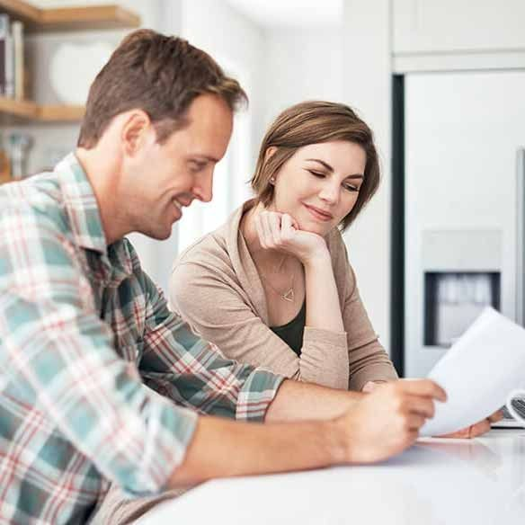 Couple looks over paperwork in kitchen