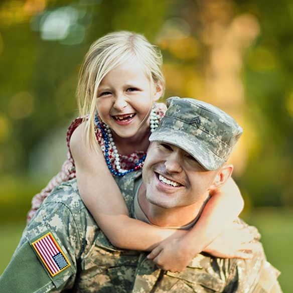VA military father in uniform with daughter on his back outdoors