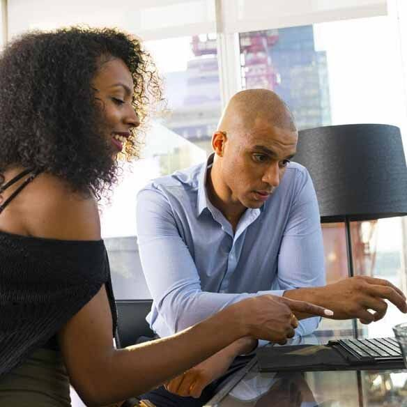 Millennial African-American couple in front of laptop