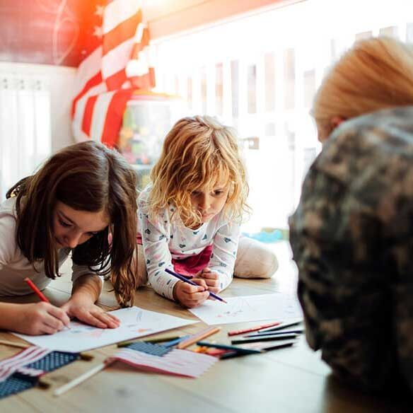 Military mother does artwork with daughters on floor