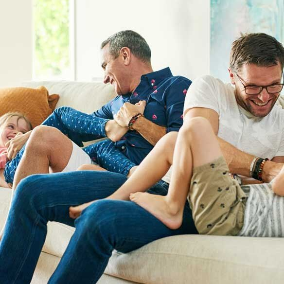 LGBT couple playing with their children on couch