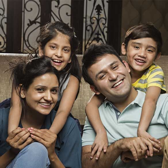 South Asian family smiling indoors