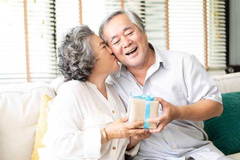Asian woman giving Asian man a gift