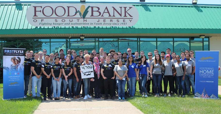 Freedom Mortgage employee volunteers standing in front of The Food Bank of South Jersey posing for a picture.