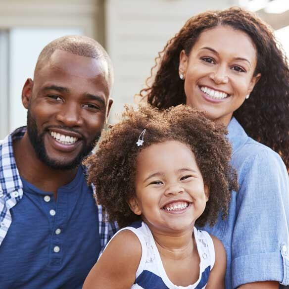 African-American family of three smiling outdoors