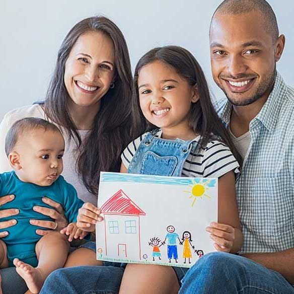 photo of multi-racial family seated in home with child's drawing