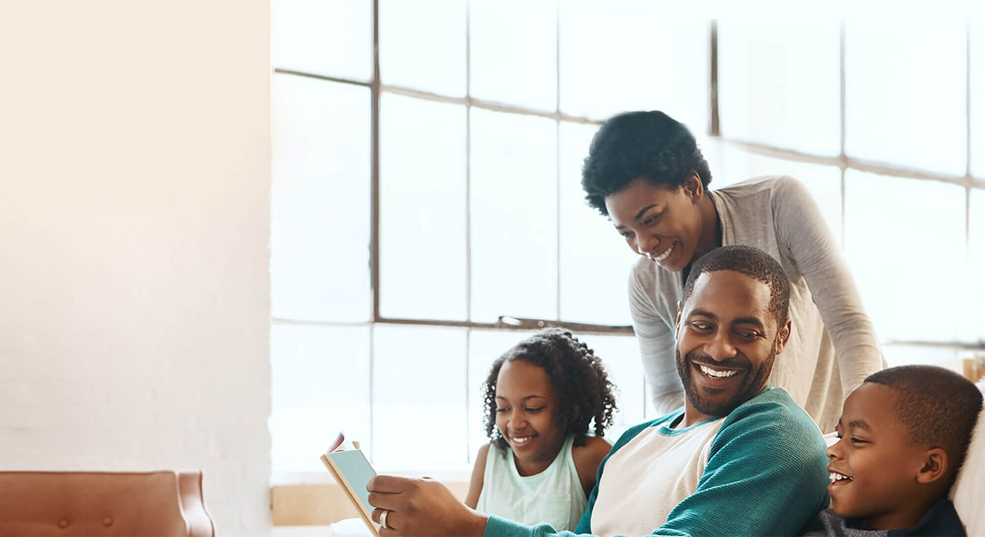Freedom Mortgage: Family in living room laughing as father reads from a book