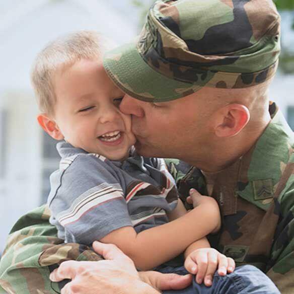 Veteran father in uniform kisses son