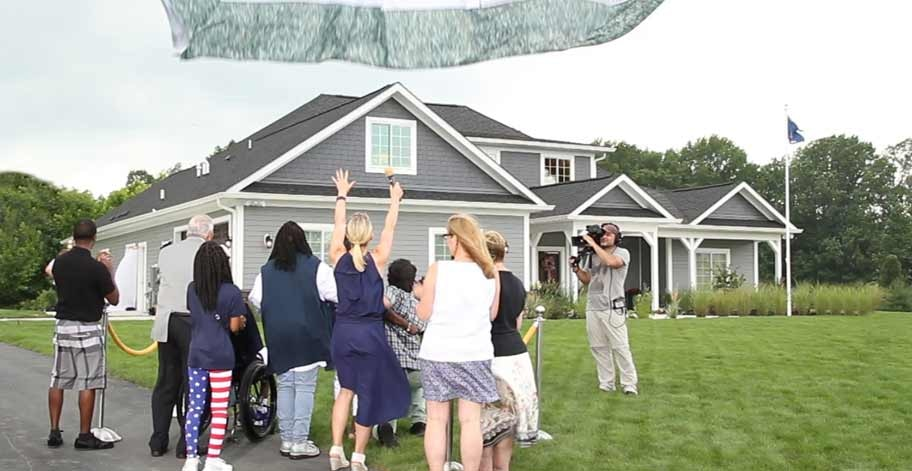 unveiling of a new house to a disabled veteran with family and television crew.