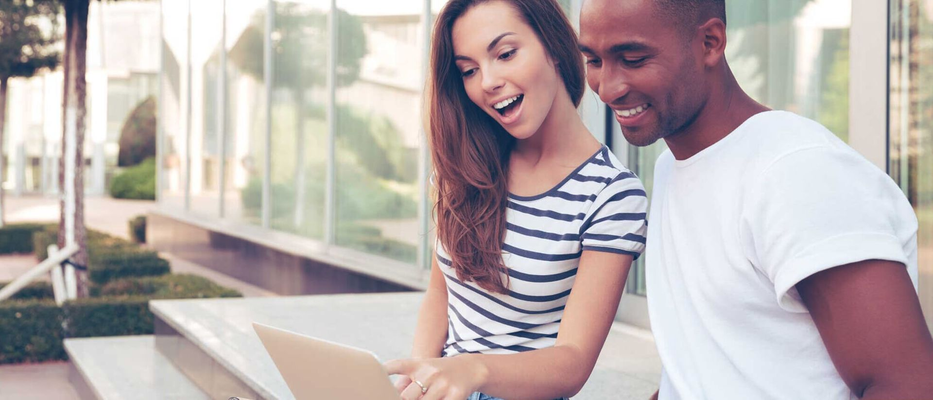 Freedom Mortgage: Young couple sitting on steps looking at laptop