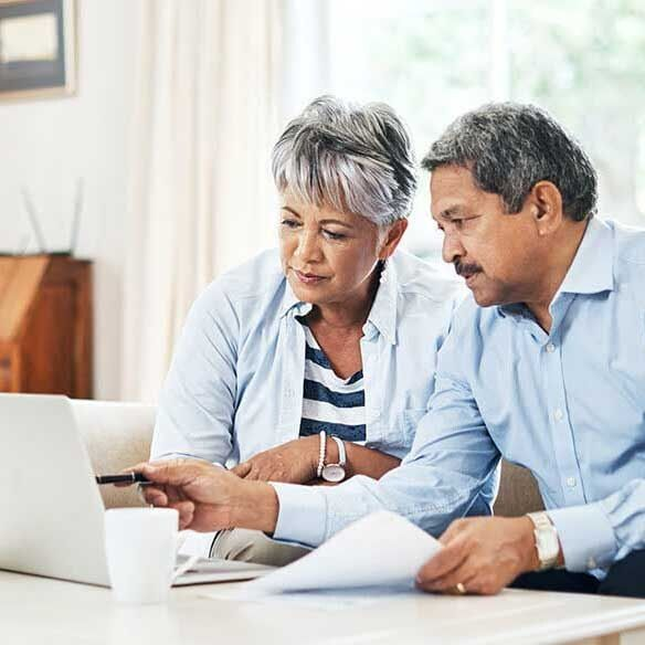 Older Hispanic couple goes over finances in front of laptop