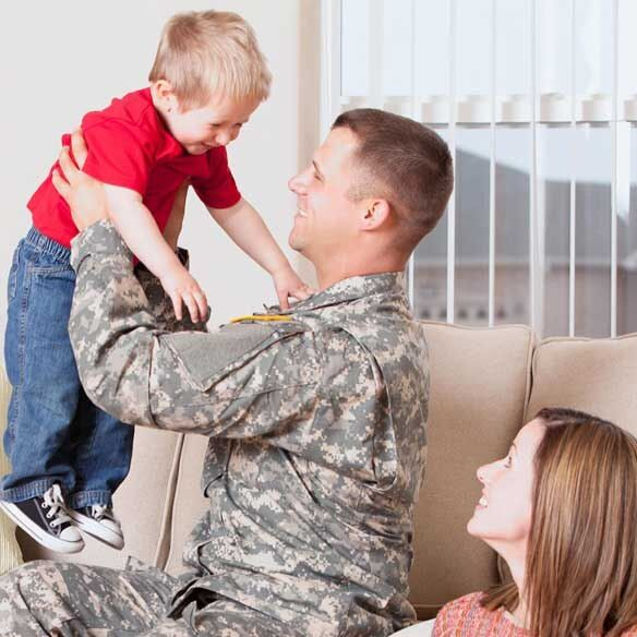 Military father in uniform with wife and son in living room