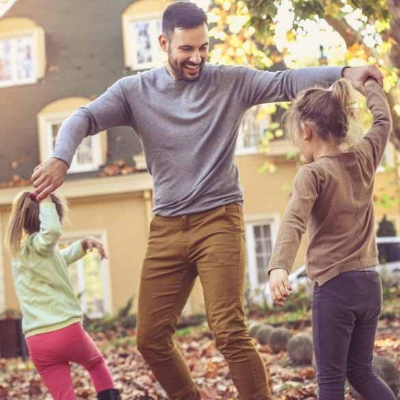 Father and daughters play in fall leaves