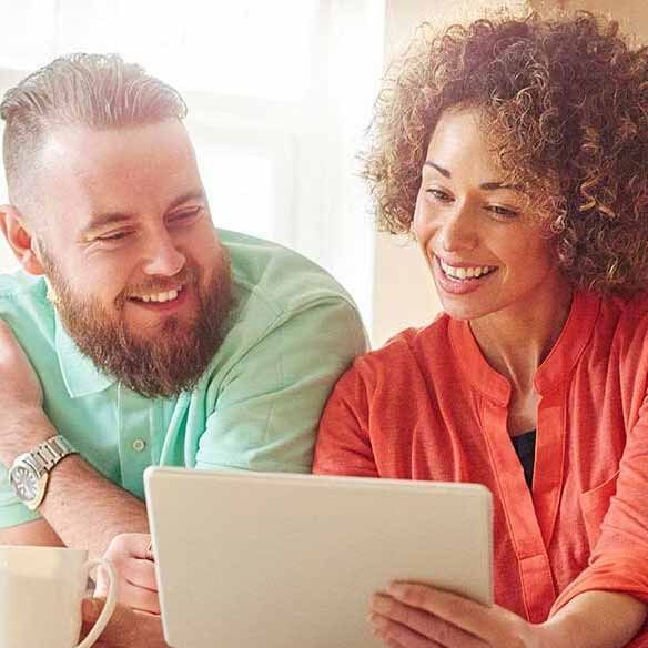 Image: Couple looks at mortgage rates on digital tablet in kitchen
