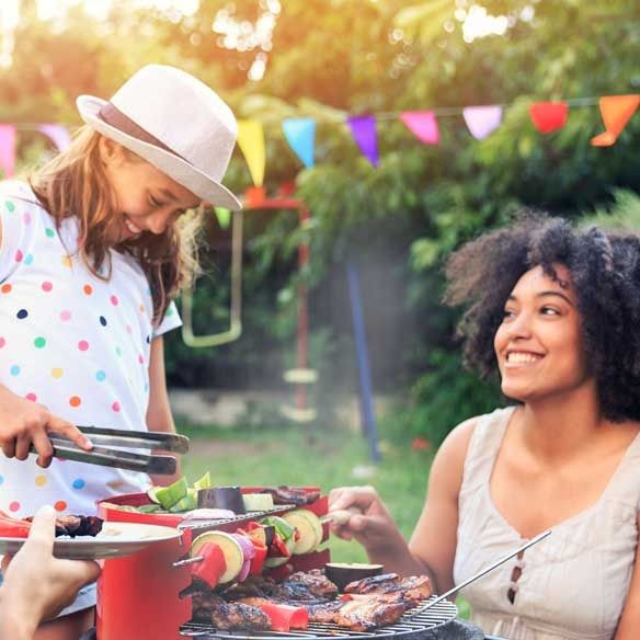 Couple has BBQ with daughter in yard
