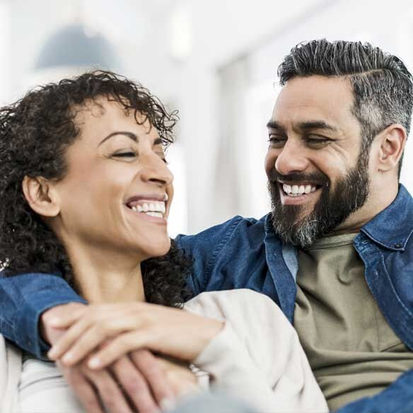 Hispanic couple laughing on couch