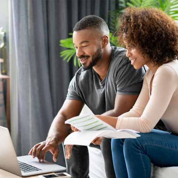 Freedom Mortgage millennial African-American couple looks over paperwork with laptop