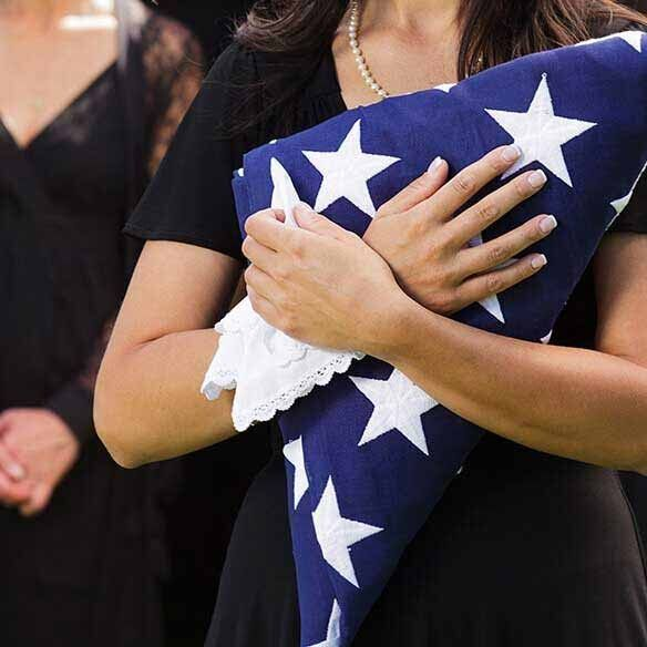 Image: Military spouse holds burial flag