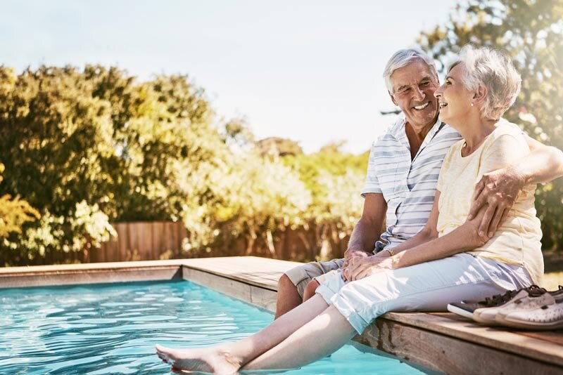 Retired couple sits by pool